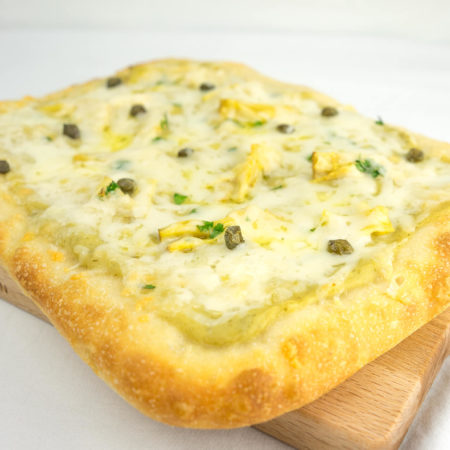 Artichoke Pizza on a wooden cutting board with white background